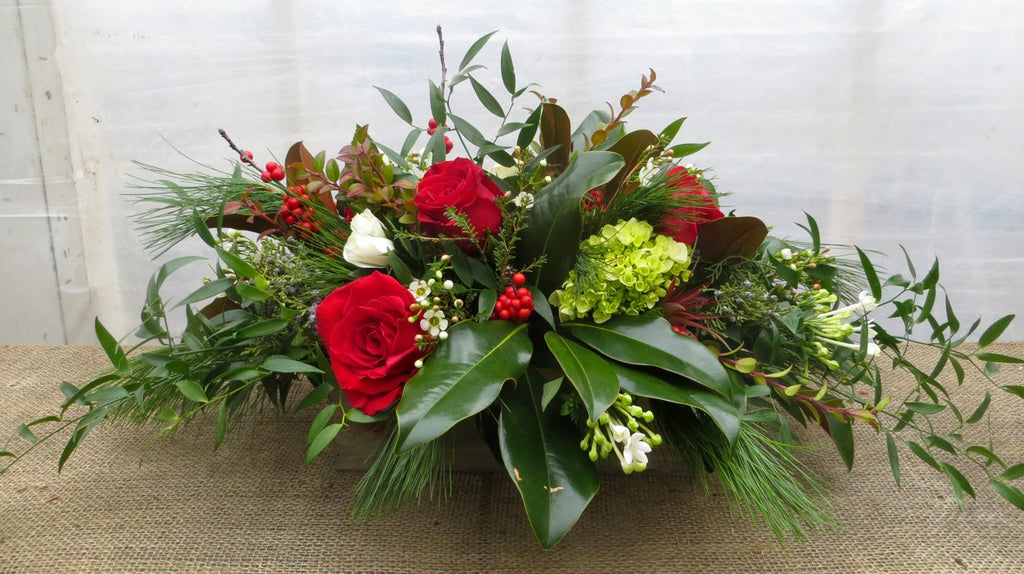 Preston: Christmas Centerpiece with Magnolia, Red Roses and Italian Ruskus. Designed by Michler's Florist in Lexington, KY
