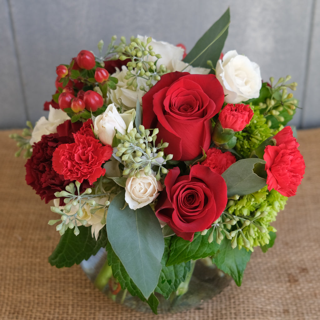 low and lush floral arrangement with roses, carnations, and seeded eucalyptus by Michler's Florist in Lexington, KY