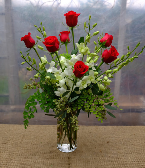 Red roses and white dendrobium orchids designed in a vase by Michler's Florist in Lexington, KY