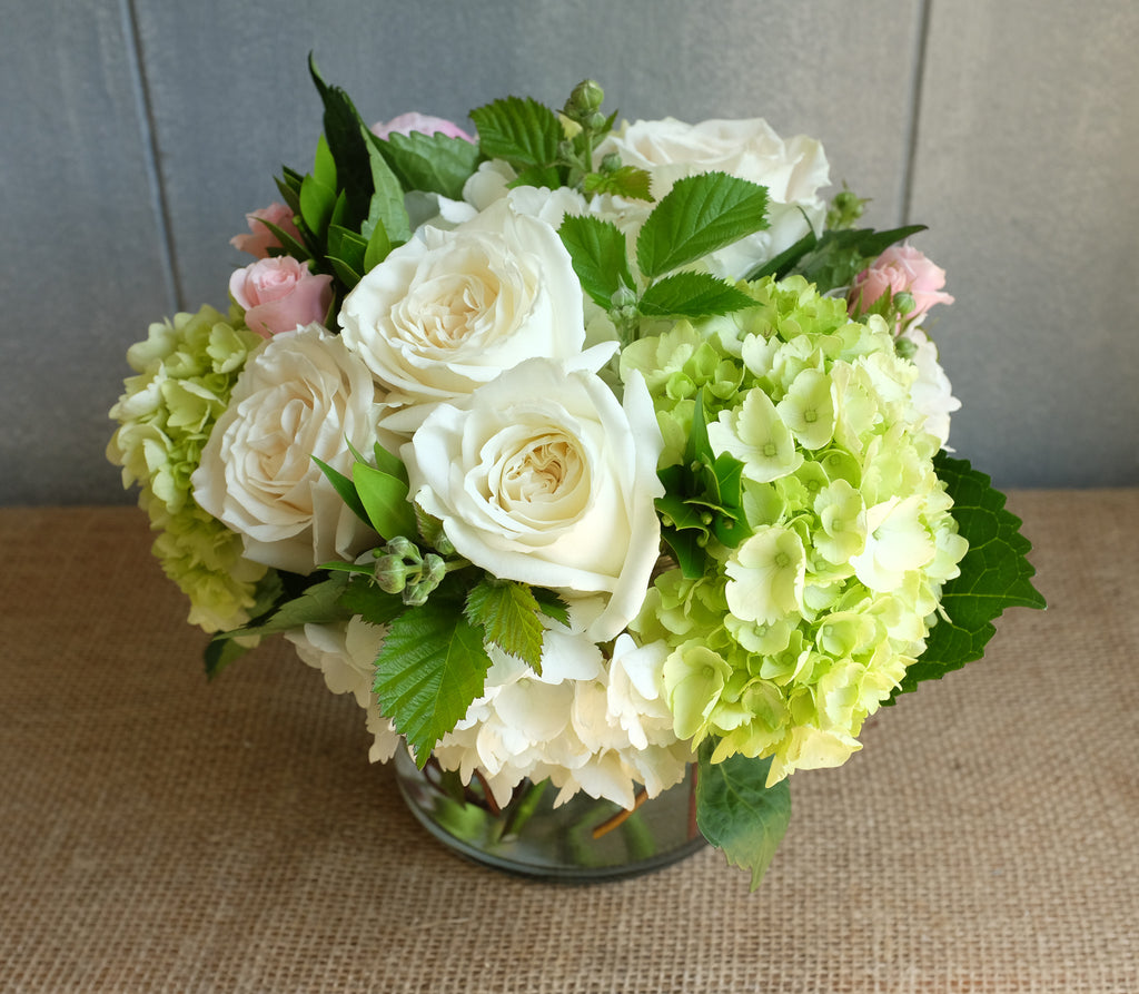 White and green bouquet of roses and hydrangea with a touch of pink.