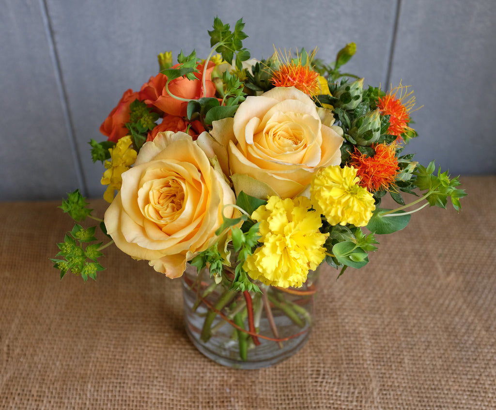 Bright floral bouquet with yellow roses and seasonal flowers in yellows and oranges