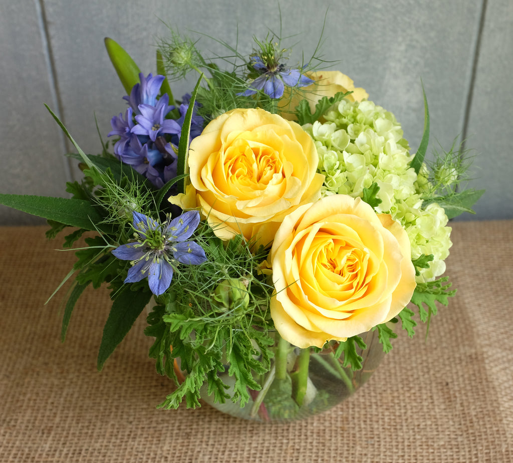 Flower arrangement with yellow roses and green hydrangea