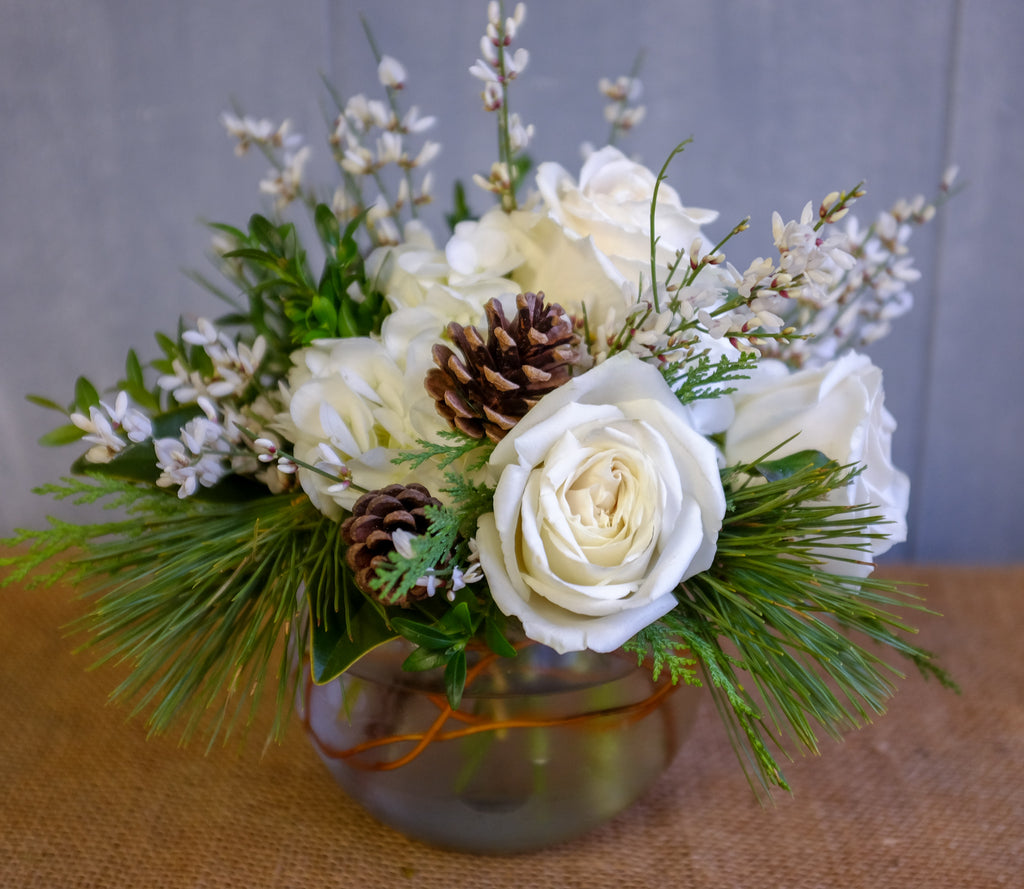 White winter flowers and evergreens and pinecones
