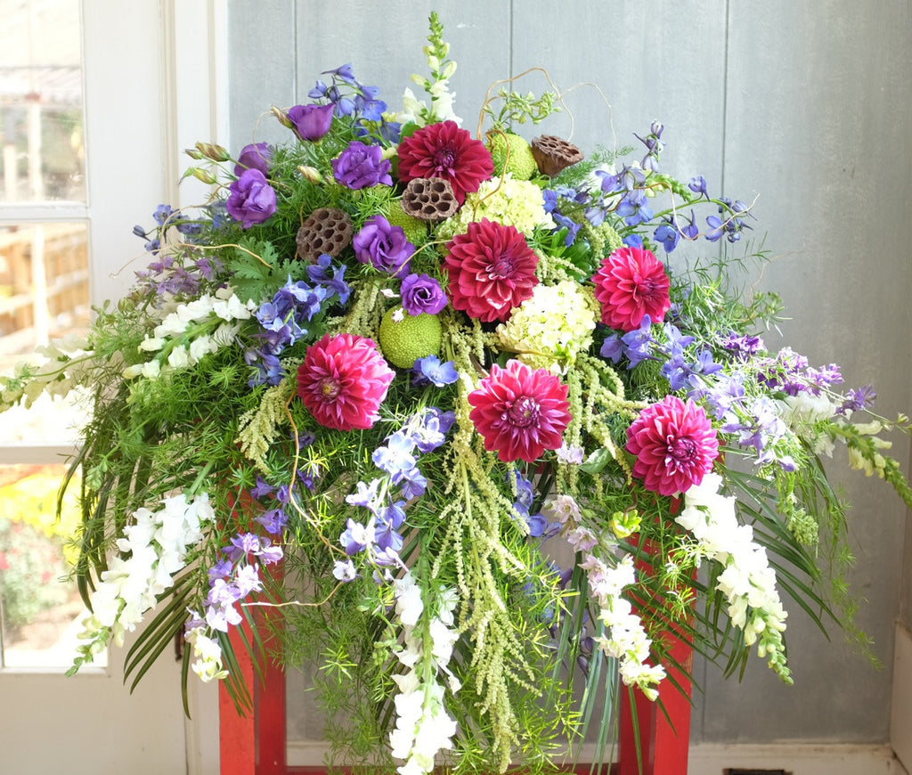 Casket Spray with Purple Dahlias, Larkspur, Lisianthus, and Snap Dragons.  Michler's Florist