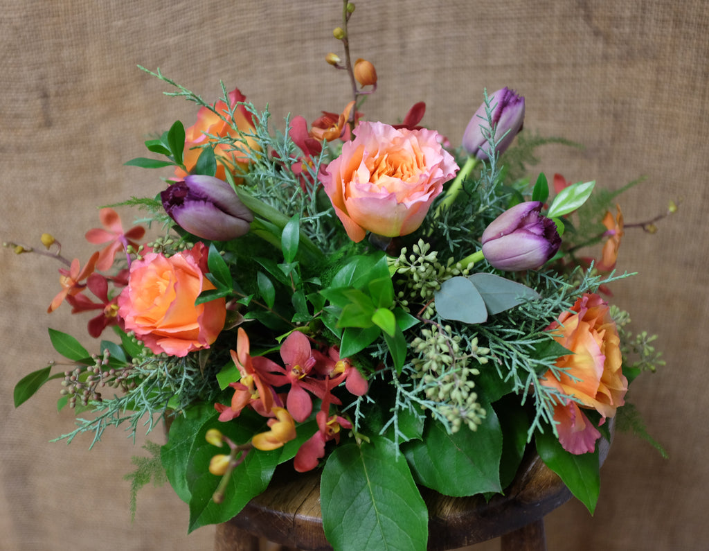 A round centerpiece in fall tones and mixed greenery