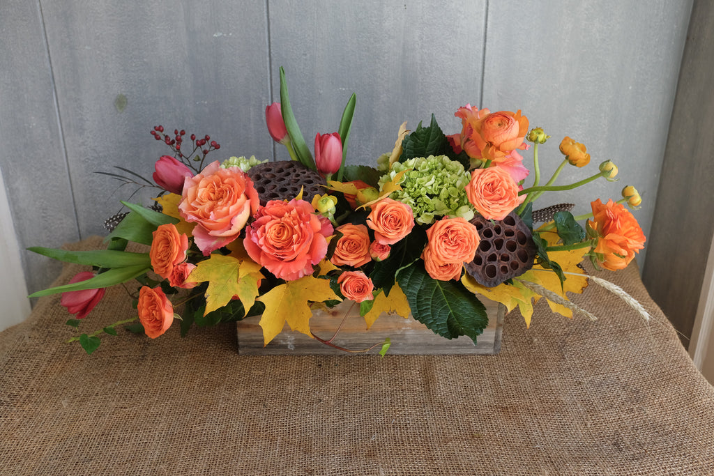 warm toned autumn arrangement with orange roses