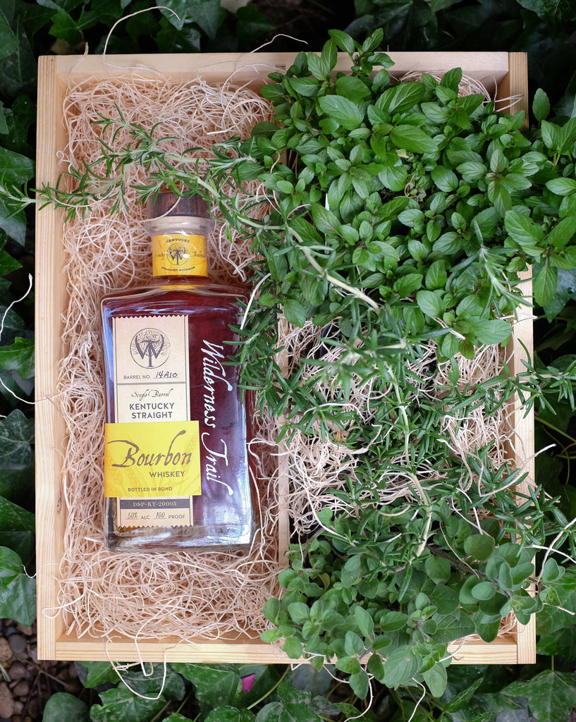 Wilderness Trail Bourbon Crate with rosemary and mint herb plants