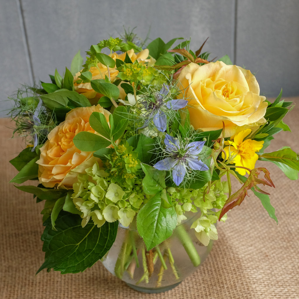 Yellow rose garden bouquet with a touch of blue.
