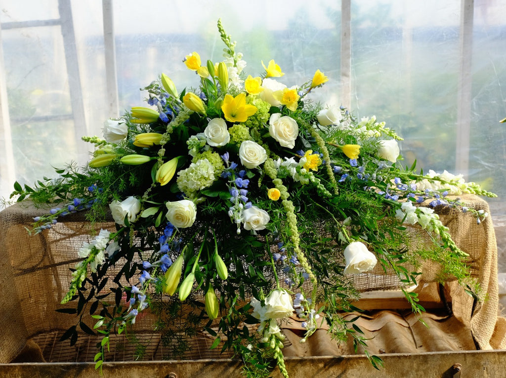 Casket Spray with Blue Delphinium, White Roses, Yellow Lilies and Yellow Freesia. Designed by Michler's Florist