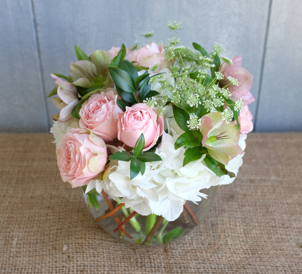 Bouquet of white hydrangea and pink roses with seasonal foliage.