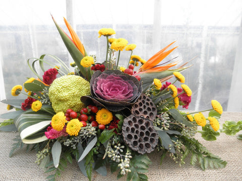 Floral arrangement by Michler's Florist with birds of paradise, ornamental cabbage, lotus seed pods