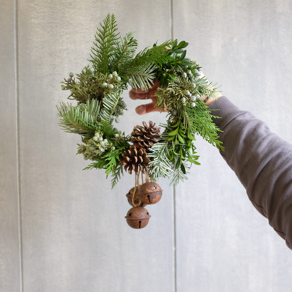 Miniature wreath with rustic jingle bells and pine cones.