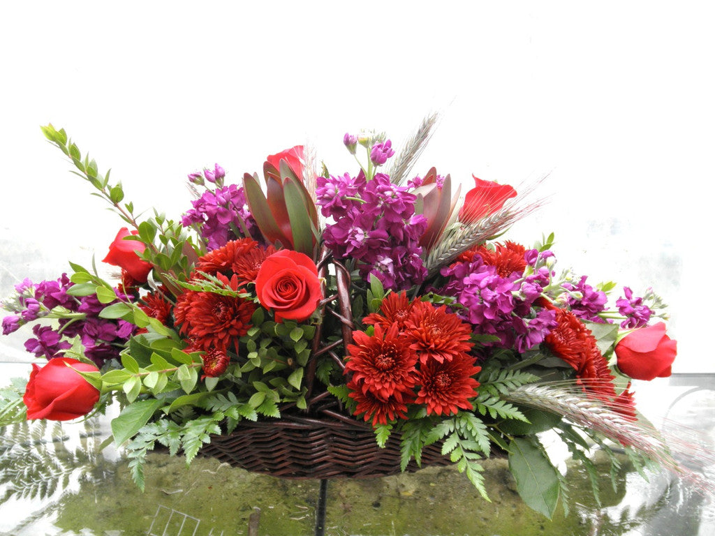Fireside Funeral Basket with Mums, Stock and Red Roses. Designed by Michler's Florist in Lexington, KY