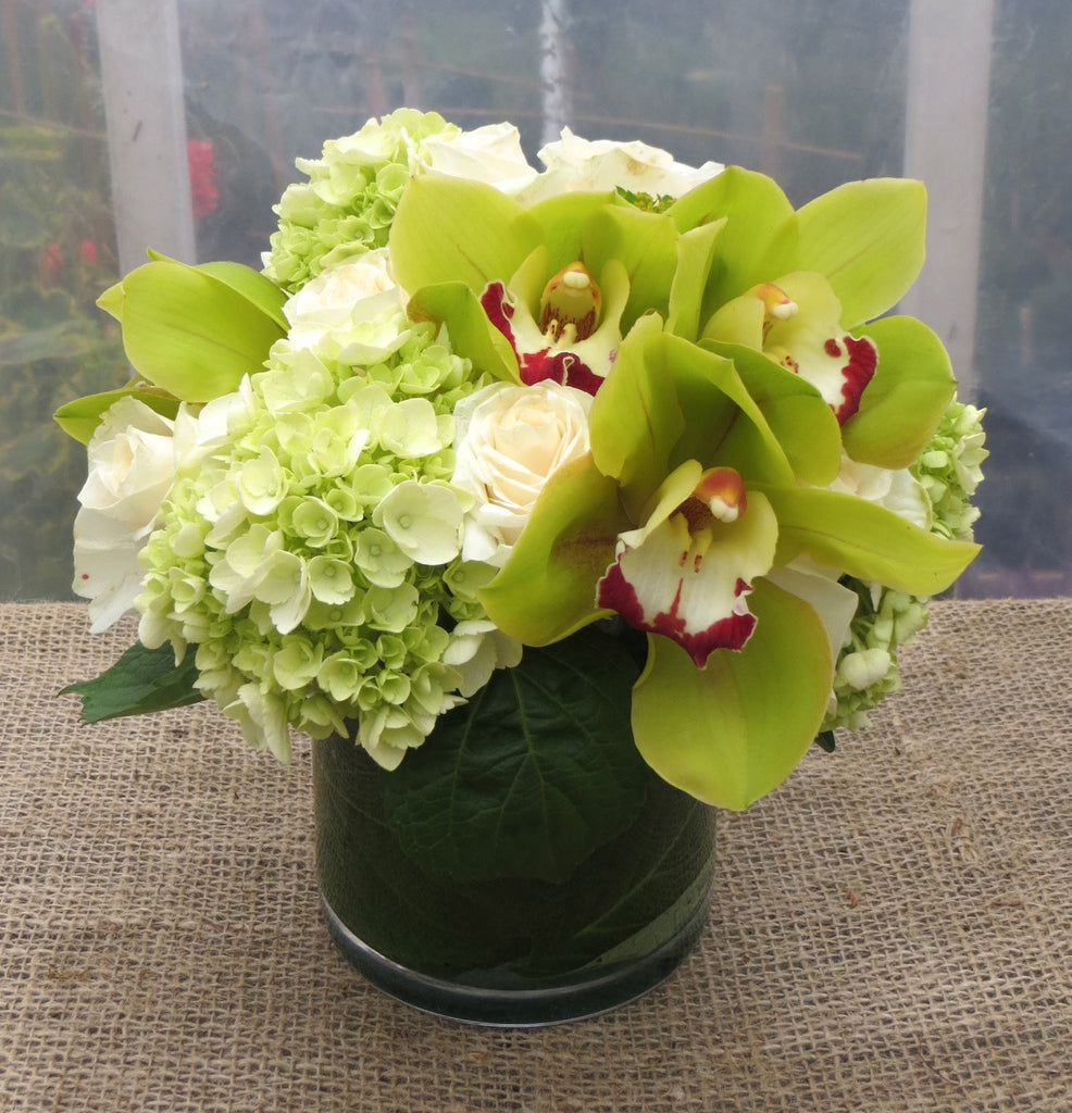 Floral arrangement with  green orchids and hydrangea by Michler's Florist