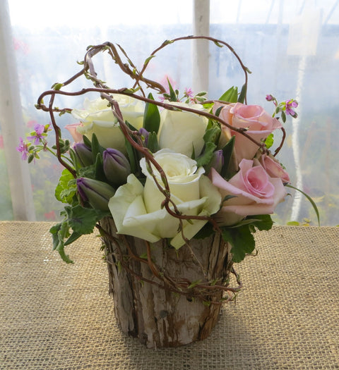 Rose arrangement in a bark pot with curly willow and tulips, designed by Michler's Florist in Lexington, KY
