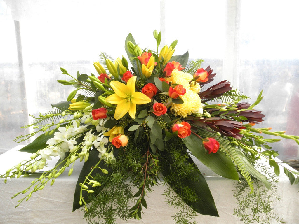 Casket Spray with Yellow Lilies, White Orchids, and Orange Roses.  Designed by Michler's Florist, Greenhouses & Garden Design