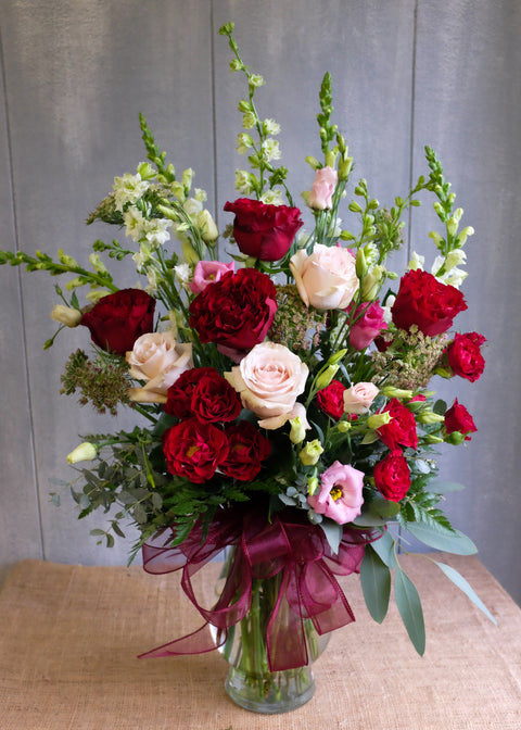 Virginia flower bouquet with red roses, pink lisianthus, and white snap dragons. Designed by Michler's Florist in