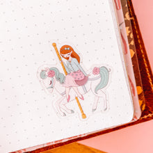 Load image into Gallery viewer, sticker of girl riding a carousel horse in a notebook