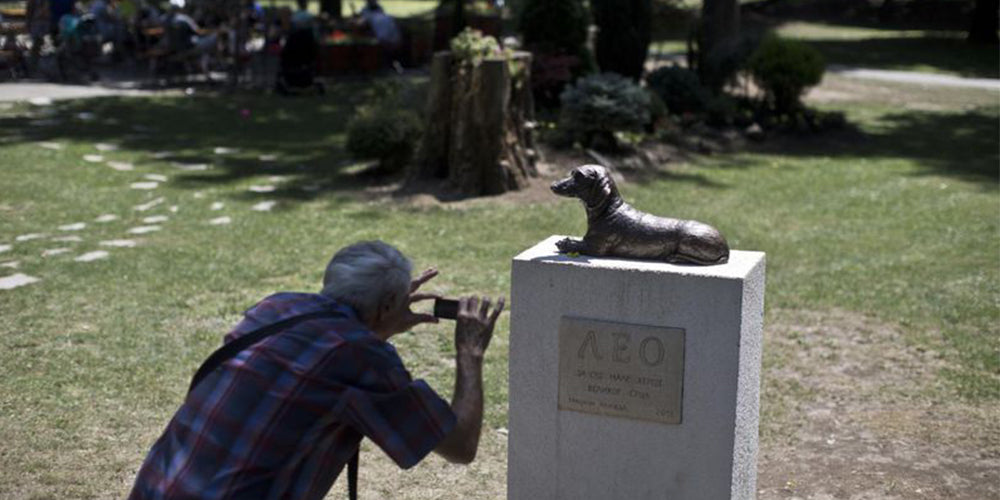 A man takes a photo of the monument to Leo, a dachshund that defended a child from an attack by another dog, at a public park in Serbia. (Marko Drobnjakovic/AP)