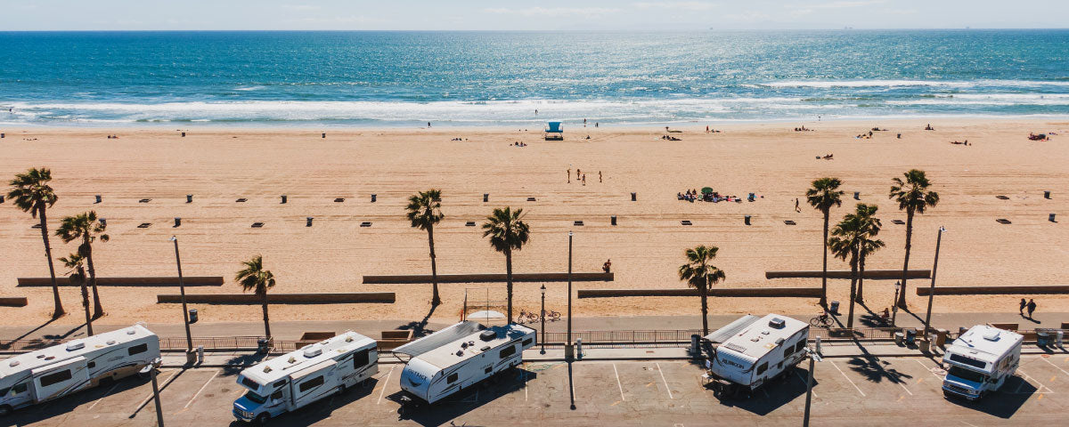 rv trailers campers parked sideways in a parking lot by the pacific ocean