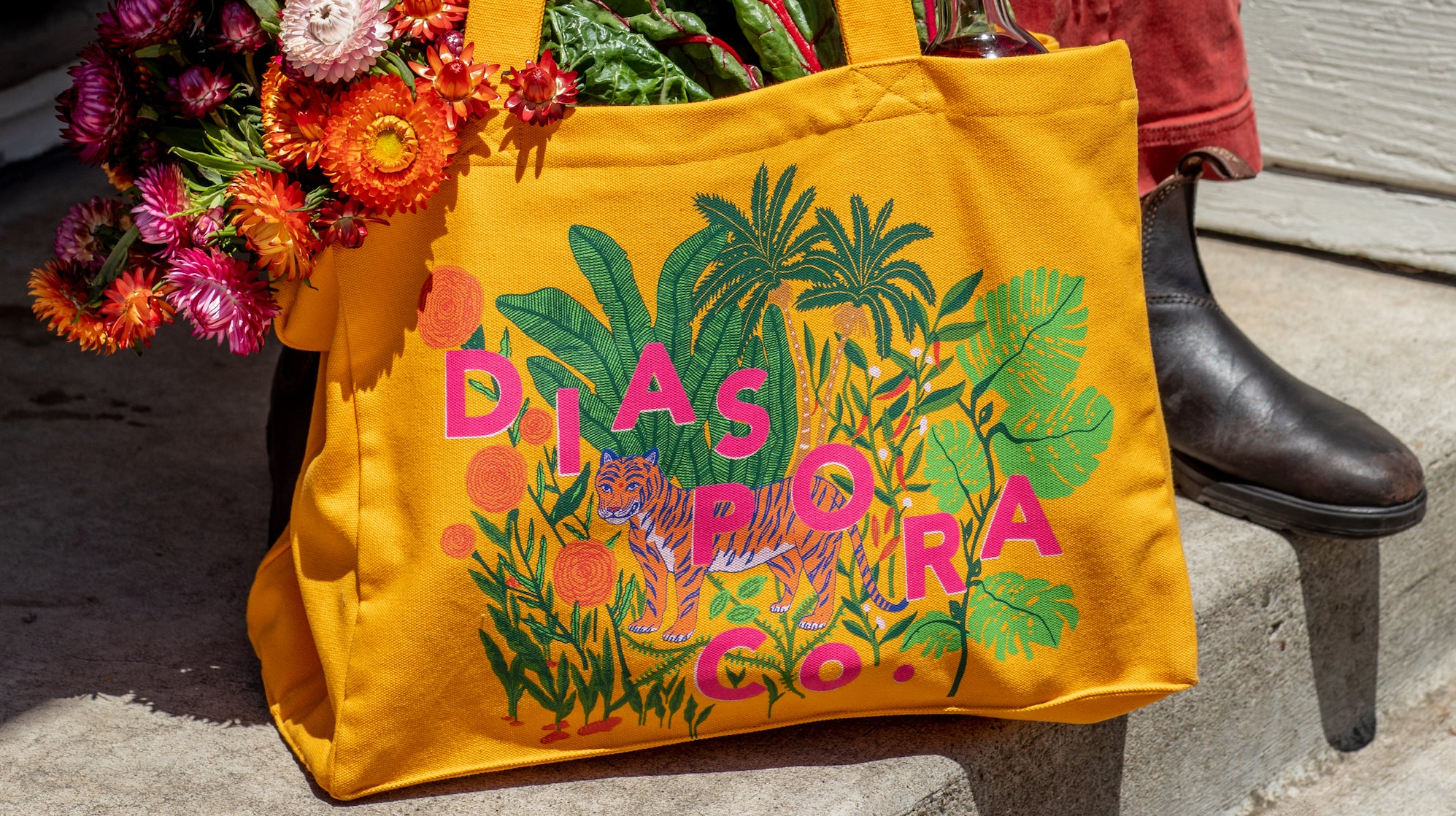 Photo of our market tote bag full of flowers and leafy greens