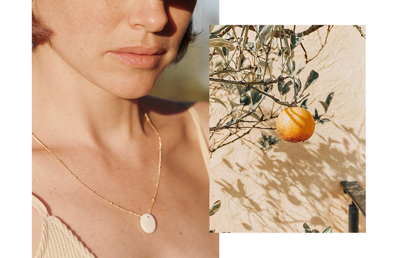 Two pictures aside, both with the perfect light. 1. Woman's portrait wearing a white clay pendant with a gold detail on a beautiful golden chain. 2. close-up of a beautiful orange on a tree.