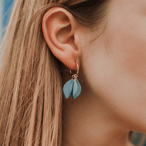 Close-up: minimal light blue porcelain earrings. Gold-filled hoops. Handmade ceramics.