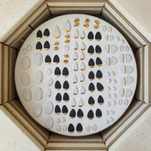 Load image into Gallery viewer, Interior of a kiln full of porcelain pieces. Black and white porcelain with hand-painted golden details.