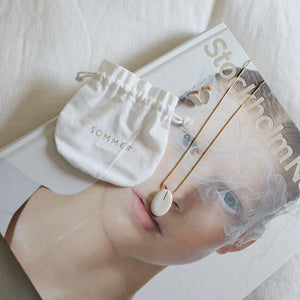 Lifestyle capture of a book and a jewellery set. Jewels made of porcelain and gold. Handmade work.