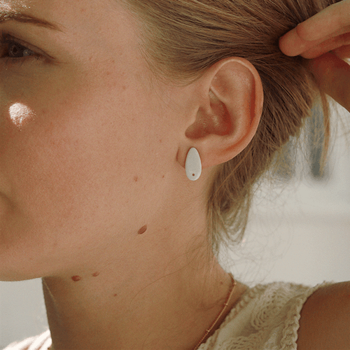 Young woman wearing tiny white and gold stud earrings. A beautiful detail for a special occasion.