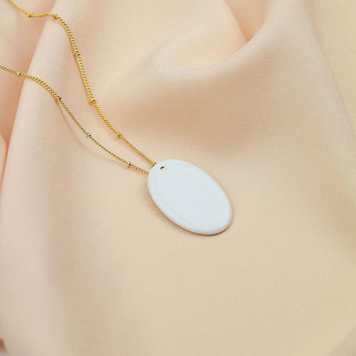 Exquisite white porcelain pendant on an elegant gold plated chain. Luminous product photography.