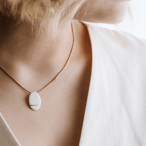 White pendant with a hand painted gold detail. Gold plated chain. Minimal jewel for every outfit.