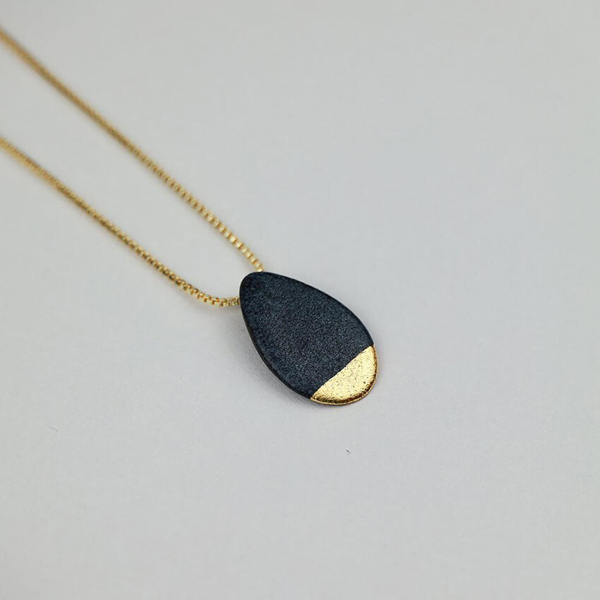 Black porcelain pendant on a gold box chain. Pottery artwork made with love for Valentine's Day.