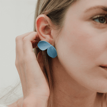 Load image into Gallery viewer, A woman wearing light blue porcelain earrings. Gold-filled studs. Handmade jewel.