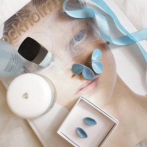 Two light blue porcelain earrings, a book, two polish nails, and skincare products.