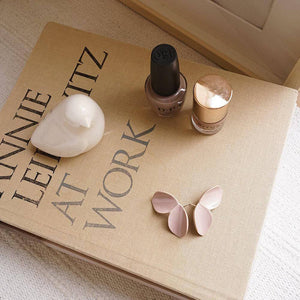 A pair of lavender earrings, a ceramic white bird, a book, and two nail polish.