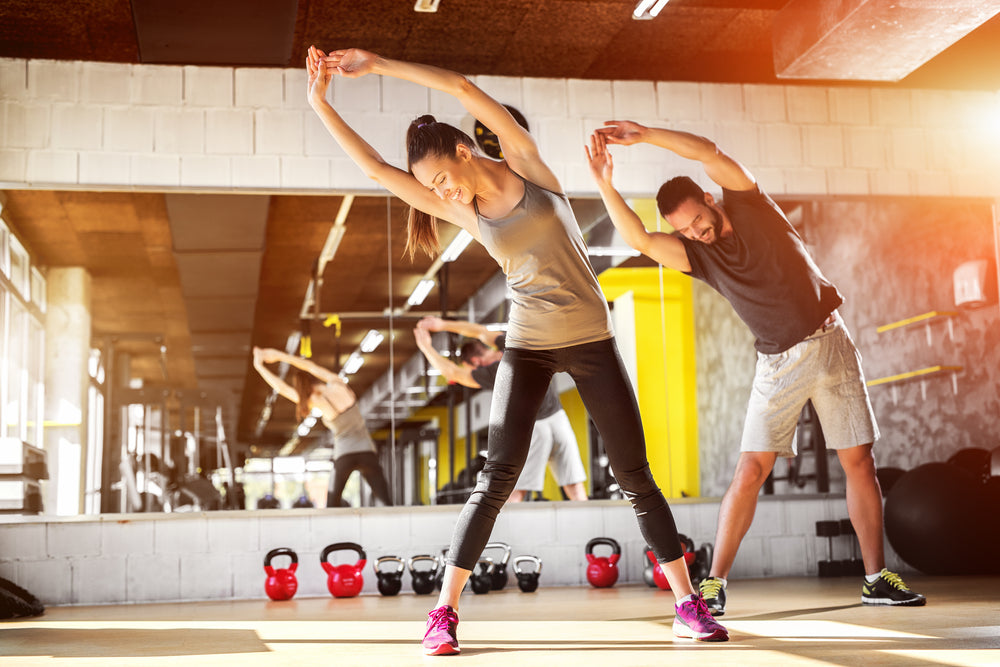 Gyms are back! Injury-free return to the gym. image of young couple stretching in the gym