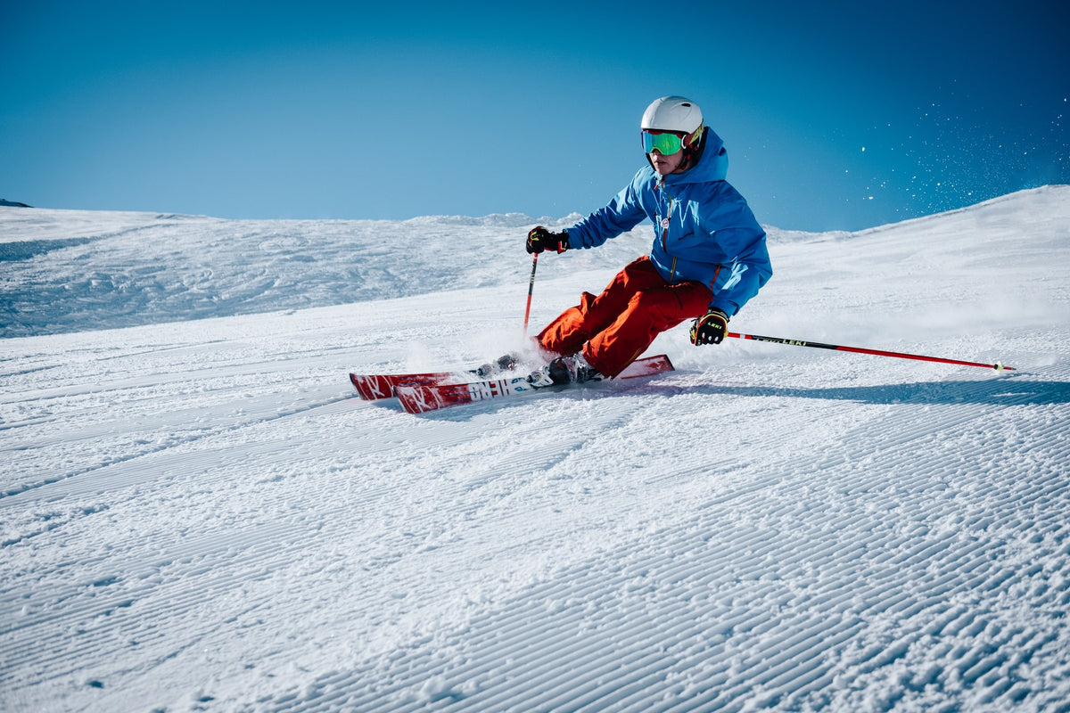How to Prevent Ankle Injuries While Skiing, image of man skiing down a mountain