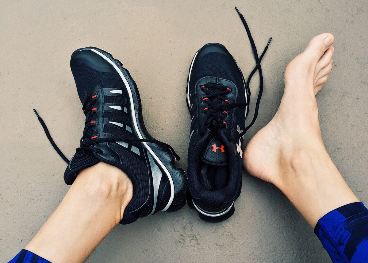 Woman wearing one sports running shoe with one shoe barefoot. Image is linked to ankle injury article. Credit: Pexels.