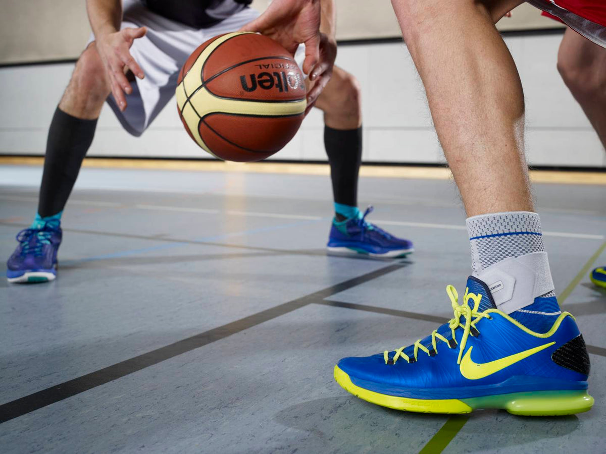 Image of two men playing basketball, one man is wearing a Bauerfeind ankle brace. Image relates to blog post with tips for selecting the right ankle brace for your injury