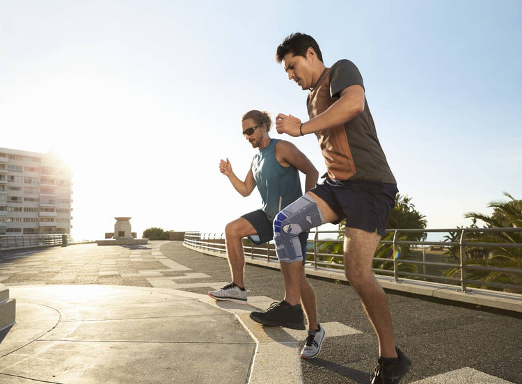 Two men doing exercises on a step, one man is wearing the Bauerfiend knee brace for strength building after injury.