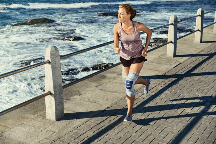 Woman with knee brace/support is running along on side-walk near the ocean