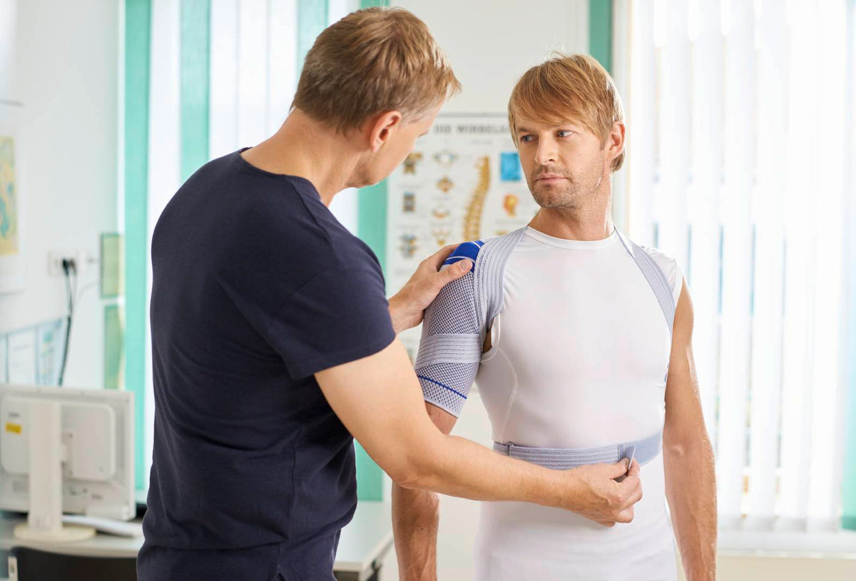 Man being fitted for the Bauerfeind OmoTrain shoulder support by a specialist