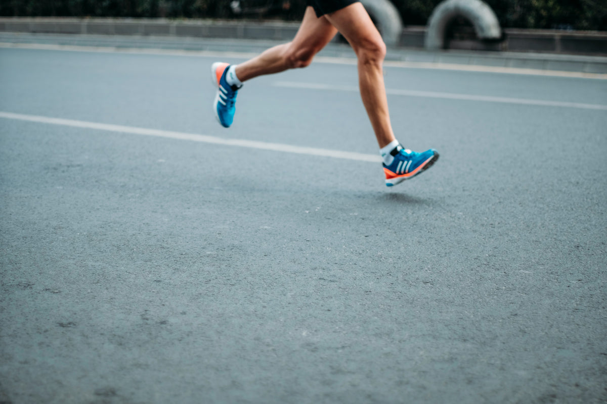 A mans legs, from the hips down. He is running down the street. How to prevent knee injury.