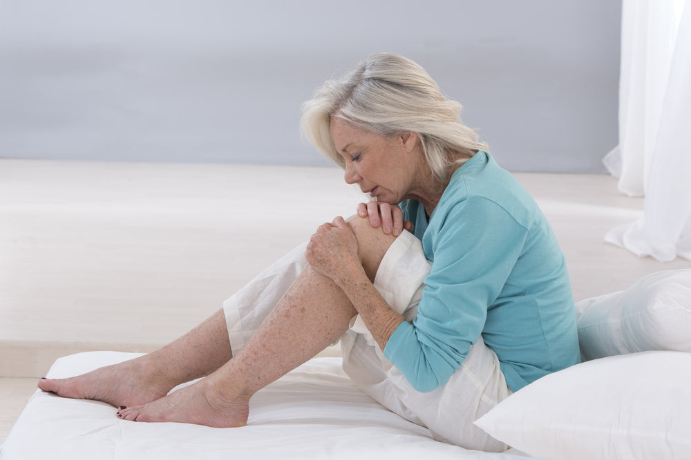 Knee Arthritis Treatment Without Surgery. Image of woman sitting on the floor holding one knee as though it is in pain.