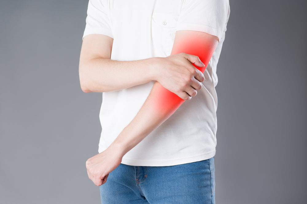 Elbow Pain: Why can't I straighten my arm? Image of man in white shirt and jeans, he is holding his left elbow and it is highlighted red to indicate pain