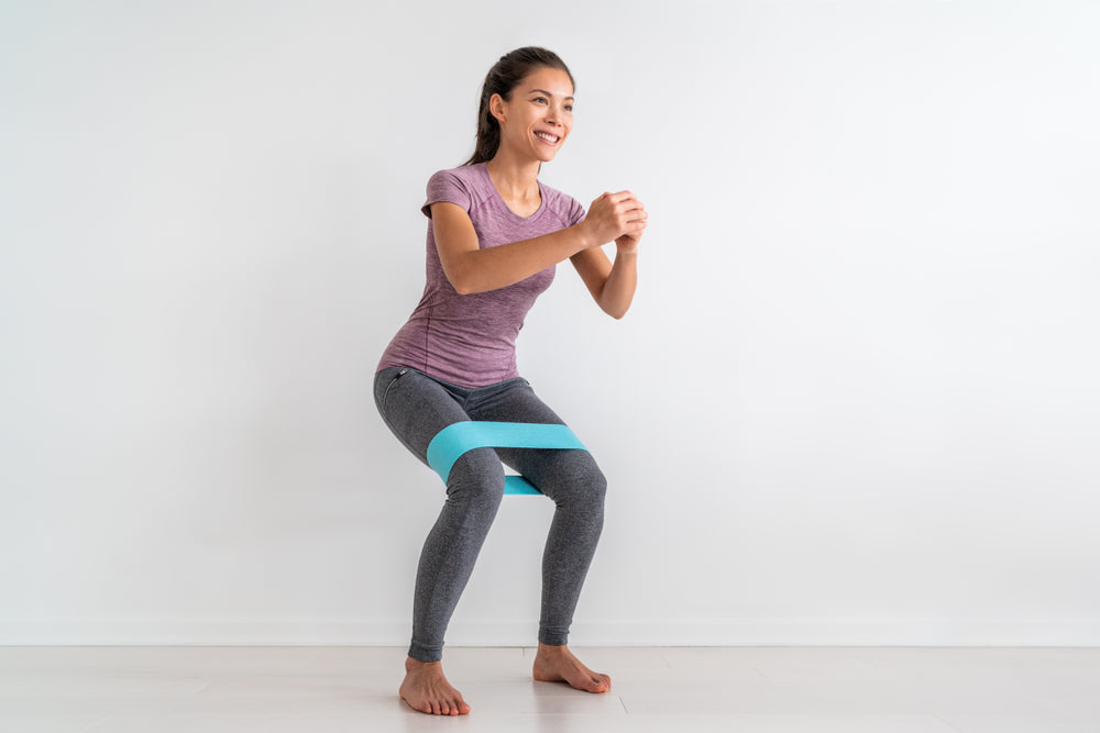 Woman wearing resistance bands to perform hip strengthening exercise