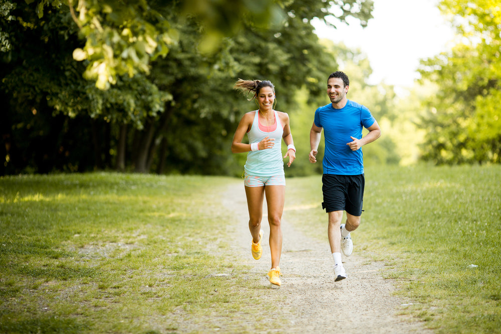 Young couple running. Running on Grass vs Concrete: Does it matter?