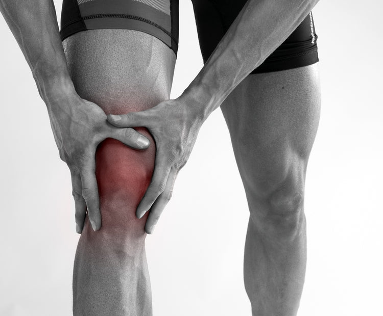 Black and white image of man holding his knee, the knee is highlight in red, indicating pain in the knee ligaments.