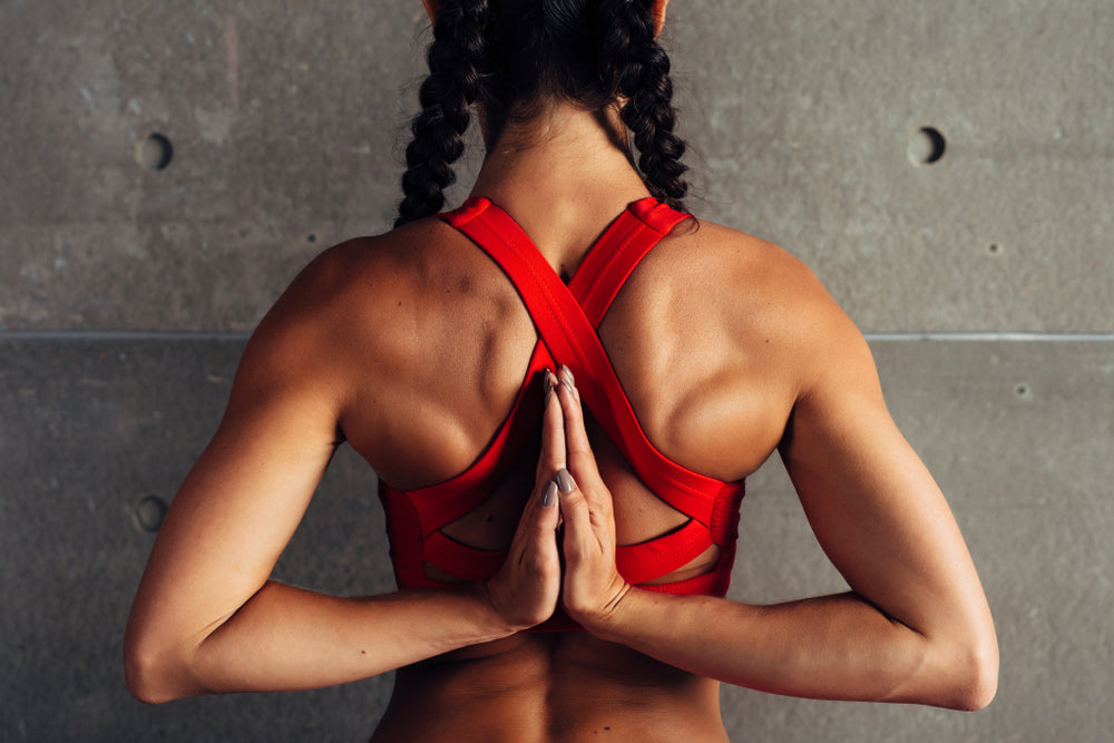 Image of woman who is able to hyper-extend her shoulders to touch her hands in the prayer position, behind her back. Being able to hyper-extend your joints in this way is related to Ehlers-Danlos Syndrome